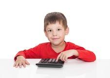 Η πενταετής συνεδρίαση αγοριών σε έναν λευκό πίνακα και τους Τύπους ο υπολογιστής κουμπιών Στοκ Εικόνες