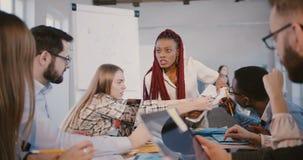 Η πεπειραμένη μοντέρνη επιχειρησιακή γυναίκα αφροαμερικάνων εργάζεται μαζί με τους ευτυχείς multiethnic υπαλλήλους στο σύγχρονο γ απόθεμα βίντεο