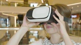 Η περίεργη κατάπληκτη γυναίκα βγάζει το κράνος VR απόθεμα βίντεο