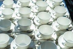 Η περίληψη θόλωσε πολλές σειρές των φλυτζανιών τσαγιού καφέ με το διανομέα καφέ Στοκ εικόνες με δικαίωμα ελεύθερης χρήσης