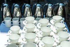 Η περίληψη θόλωσε πολλές σειρές των φλυτζανιών τσαγιού καφέ με το διανομέα καφέ Στοκ Φωτογραφία