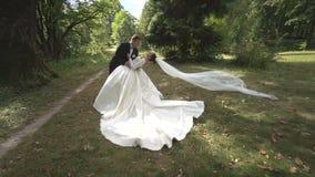 Η περιβάλλοντας κάμερα γύρω από ευτυχή το μοντέρνο το ζεύγος που αγκαλιάζει στο δάσος που το πέπλο της νύφης κινείται από τον αέρ απόθεμα βίντεο