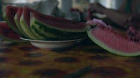 Η περικοπή σχεδίων κινηματογραφήσεων σε πρώτο πλάνο στο ώριμο καρπούζι κομματιών βρίσκεται σε έναν πίνακα σε ένα πιάτο απόθεμα βίντεο
