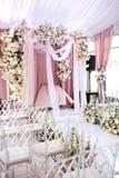 Η περιοχή γαμήλιας τελετής είναι διακοσμημένη με το λευκό και το ύφασμα ροδάκινων, πολυέλαιος κρυστάλλου, διαφανείς καρέκλες για  στοκ εικόνες