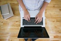 Η περιστασιακή επιχειρησιακή γυναίκα εργάζεται on-line στο lap-top που δίνουν στο Κ Στοκ εικόνες με δικαίωμα ελεύθερης χρήσης