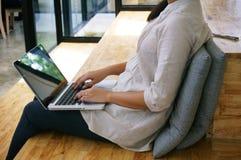 Η περιστασιακή επιχειρησιακή γυναίκα εργάζεται on-line στο lap-top που δίνουν στο Κ Στοκ Φωτογραφία