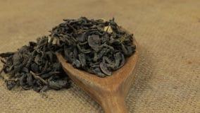 Η περιστροφή, σωροί ξηρού βγάζει φύλλα το πράσινο τσάι που πέφτει από ένα ξύλινο κουτάλι burlap απόθεμα βίντεο