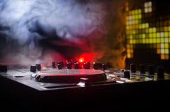 Η περιστροφή του DJ, η μίξη, και το γρατσούνισμα σε μια λέσχη νύχτας, χέρια των διάφορων ελέγχων διαδρομής τσιμπημάτων του DJ στη Στοκ Φωτογραφία