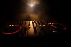 Η περιστροφή του DJ, η μίξη, και το γρατσούνισμα σε μια λέσχη νύχτας, χέρια των διάφορων ελέγχων διαδρομής τσιμπημάτων του DJ στη Στοκ Εικόνες