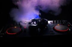 Η περιστροφή του DJ, η μίξη, και το γρατσούνισμα σε μια λέσχη νύχτας, χέρια των διάφορων ελέγχων διαδρομής τσιμπημάτων του DJ στη Στοκ Φωτογραφίες
