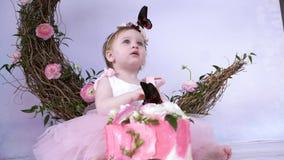 Η πεταλούδα κάθεται στο κεφάλι ενός όμορφου μικρού κοριτσιού στο βλαστό φωτογραφιών ενάντια στο σκηνικό ενός ντεκόρ στο εσωτερικό απόθεμα βίντεο
