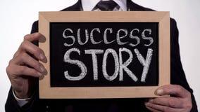 Η πετυχημένη ιστορία που γράφεται επιχείρηση στον πίνακα στα χέρια επιχειρηματιών, ξεκινά τη νέα στοκ φωτογραφίες