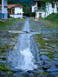 Η πηγή καθαρού νερού σε μια πέτρα έστρωσε το δρόμο με τη θολωμένη πόλη στην κατακόρυφο υποβάθρου Στοκ Φωτογραφία
