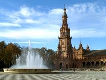 Η πηγή και ο ζαλίζοντας πύργος Plaza de Espana κάτω από το νεφελώδη μπλε ουρανό, Σεβίλη Στοκ Εικόνες