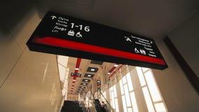 Η πινακίδα στο κτήριο σταθμών και οι άνθρωποι αναρριχούνται επάνω στην κυλιόμενη σκάλα φιλμ μικρού μήκους