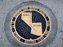 Η πινακίδα χαλκού χαρακτηρίζει την κρατική γραμμή της Αριζόνα - της Νεβάδας Στοκ Φωτογραφίες