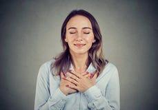 Η πιστή γυναίκα με τις προσοχές ιδιαίτερες κρατά τα χέρια στο στήθος κοντά στην καρδιά, παρουσιάζει ευγένεια στοκ φωτογραφία με δικαίωμα ελεύθερης χρήσης