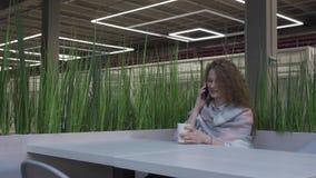 Η πλάγια όψη μιας νέας και όμορφης γυναίκας με την κόκκινη τρίχα που κάθεται σε έναν καφέ παίρνει το τηλέφωνο απόθεμα βίντεο