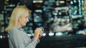 Η πλάγια όψη της καυκάσιας μέσης ηλικίας γυναίκας χρησιμοποιεί ένα smartphone στο υπόβαθρο των φω'των του Μανχάταν απόθεμα βίντεο