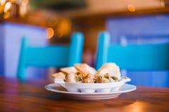 Η πλάγια όψη του συνόλου πιάτων του συνόλου κοχυλιών σαλιγκαριών του χαβιαριού στο θολωμένο υπόβαθρο του εστιατορίου Στοκ Φωτογραφία