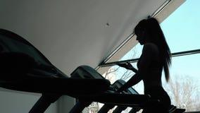 Η πλάτη σκιαγραφιών μιας γυναίκας παίρνει έτοιμη για ένα τρέξιμο treadmill, πρωί εκπαιδευτικός το υγιές κατάλληλο μεμβρανοειδές κ φιλμ μικρού μήκους