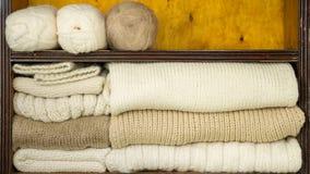 Η πλήρωση των ραφιών από τις σφαίρες του μαλλιού, πλέκοντας βελόνες, τελείωσε τα μάλλινα υφάσματα απόθεμα βίντεο