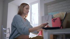 Η πληρωμή Διαδικτύου, όμορφο αναμένον θηλυκό με την πιστωτική κάρτα χρησιμοποιεί το φορητό προσωπικό υπολογιστή για τις σε απευθε απόθεμα βίντεο