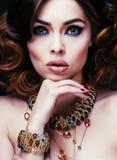 Η πλούσια γυναίκα ομορφιάς με τα κοσμήματα πολυτέλειας μοιάζει με ώριμο Στοκ Εικόνες