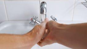 Η πλύση ατόμων παραδίδει το νεροχύτη κάτω από το τρεχούμενο νερό από τη βρύση φιλμ μικρού μήκους