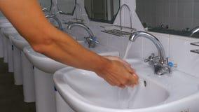 Η πλύση ατόμων παραδίδει το νεροχύτη κάτω από το τρεχούμενο νερό από τη βρύση απόθεμα βίντεο