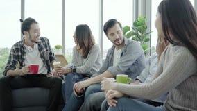 Η ποικιλομορφία των νέων ομαδοποιεί τα φλυτζάνια καφέ εκμετάλλευσης ομάδων και συζήτηση κάτι με το χαμόγελο καθμένος στον καναπέ  απόθεμα βίντεο