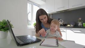 Η πολλαπλών καθηκόντων μητρότητα, επιχειρησιακό θηλυκό συνδυάζει το αγοράκι και την εργασία ανατροφής στο φορητό προσωπικό υπολογ απόθεμα βίντεο