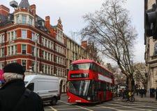 Η πολυάσχολη διατομή του Λονδίνου τη συννεφιάζω υγρή χειμερινή ημέρα με τους ανθρώπους στα ποδήλατα και το διπλό κατάστρωμα μεταφ στοκ εικόνα