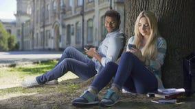 Η πολυεθνική ανταλλαγή τύπων και κοριτσιών σύντομη κοιτάζει, καθμένος κάτω από το δέντρο με τα τηλέφωνα απόθεμα βίντεο