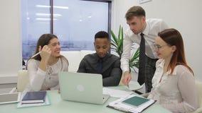 Η πολυεθνική επιχειρησιακή ομάδα είναι 'brainstorming' στο γραφείο μπροστά από το lap-top απόθεμα βίντεο