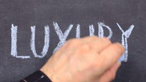 Η ΠΟΛΥΤΕΛΕΙΑ λέξης, γραπτή κοντά παραδίδει την κιμωλία σε έναν πίνακα φιλμ μικρού μήκους