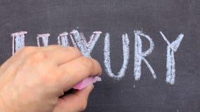 Η ΠΟΛΥΤΕΛΕΙΑ λέξης, γραπτή κοντά παραδίδει την κιμωλία σε έναν πίνακα απόθεμα βίντεο