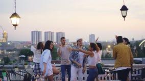 Η πολυφυλετική ομάδα φίλων χορεύει στη στέγη που έχει το δροσερό κόμμα με το DJ το βράδυ το καλοκαίρι Χαρούμενη νεολαία απόθεμα βίντεο