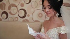 Η πολύ όμορφη νύφη ανοίγει και διαβάζει μια επιστολή από αγαπημένη φιλμ μικρού μήκους