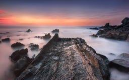 Η πορεία βράχου στον ωκεανό, σχετικά με ένα ζωηρόχρωμο ηλιοβασίλεμα Στοκ Φωτογραφίες