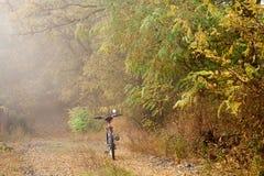 Η πορεία στο δάσος φθινοπώρου και το ποδήλατο hardtail Ποδήλατο που βρίσκεται στο έδαφος στο δάσος Στοκ εικόνα με δικαίωμα ελεύθερης χρήσης