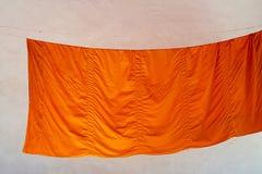 Η πορτοκαλιά τήβεννος του βουδιστικού μοναχού είναι ξηρά σε ένα σχοινί στοκ εικόνα με δικαίωμα ελεύθερης χρήσης