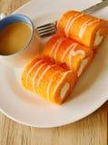 Η πορτοκαλιά γεμισμένη ρόλος κρέμα μαρμελάδας τρώει το ζεύγος με τον καφέ στο πιάτο Στοκ εικόνα με δικαίωμα ελεύθερης χρήσης