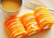 Η πορτοκαλιά γεμισμένη ρόλος κρέμα μαρμελάδας τρώει το ζεύγος με τον καφέ στο πιάτο Στοκ Εικόνες