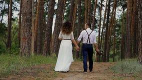 Η πολυτέλεια το ζεύγος πηγαίνει μακριά στις δασικές έπειτα στροφές πεύκων γύρω και αγκαλιάζοντας η μια την άλλη Ενάντια στο σκηνι απόθεμα βίντεο