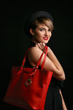 Η πολύ μοντέρνη γυναίκα που κρατά τη fansy κόκκινη τσάντα επιθυμεί να χαμογελάσει και να θέσει σε μια κάμερα Στοκ φωτογραφίες με δικαίωμα ελεύθερης χρήσης