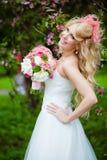 Η πολύ όμορφη ευτυχής ξανθή σγουρή τρίχα νυφών σε ένα λευκό ντύνει Στοκ Φωτογραφίες
