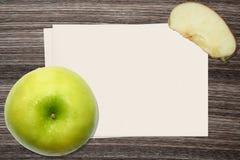 Η πράσινα Apple και και έγγραφο για το ξύλινο υπόβαθρο Στοκ Εικόνες