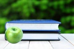 Η πράσινες Apple και βίβλοι στον ξύλινο πίνακα στη φύση Στοκ Φωτογραφίες