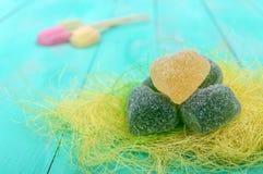 Η πράσινη και κίτρινη καρδιά καραμελών ζελατίνας διαμόρφωσε τη διακόσμηση ζάχαρης σε ένα φωτεινό υπόβαθρο άνοιξη Στοκ Φωτογραφίες
